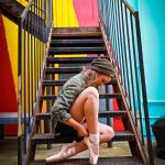 girl sitting on stairs with pointe dance shoes on