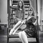 two woodward dancers sitting on stairs posing